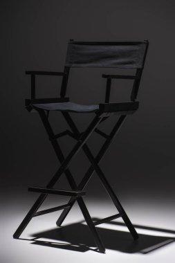 Modern, black filmmaker chair on dark grey background, cinema concept stock vector