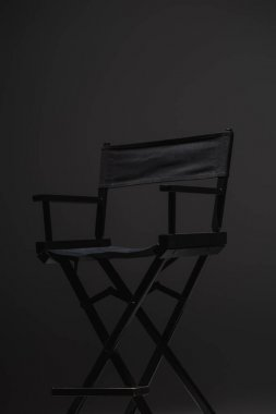 Black, modern director chair on dark grey background, cinema concept stock vector