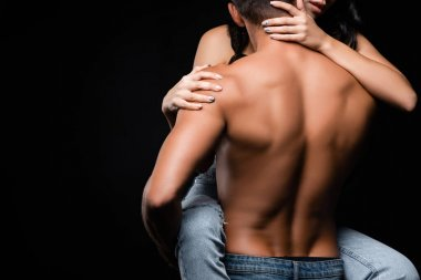 Cropped view of muscular man holding girlfriend in jeans isolated on black
