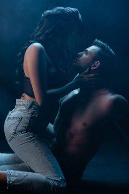 Sensual woman sitting on shirtless boyfriend on black background with smoke