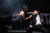 Man holding glass of whiskey near passionate woman in dress on couch on black background with smoke