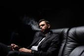 Brünette Mann in formeller Kleidung Rauchen auf Ledercouch isoliert auf schwarz