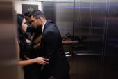 Seitenansicht eines Mannes, der verführerische Freundin im Aufzug berührt