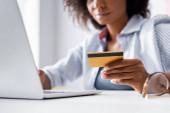 Vágott kilátás hitelkártya a kezében afro-amerikai szabadúszó laptoppal szemüveg közelében elmosódott előtérben