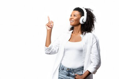 Smiling african american woman in headphones pointing with finger isolated on white