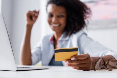 Credit card in hand of african american woman near eyeglasses and laptop on blurred background stock vector