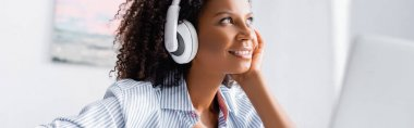 Smiling african american woman listening music in headphones near laptop on blurred foreground, banner