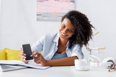 Cheerful african american teleworker holding smartphone with blank screen near laptop, headphones and cup on blurred foreground