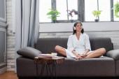 fiatal felnőtt nő ül keresztbe tett lábakkal és zenét hallgat fejhallgatóval a kanapén a nappaliban