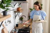 fiatal felnőtt nő tesz szeletek padlizsán serpenyőben a konyhában