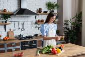 glückliche junge erwachsene Frau in Schürze bereitet Gemüsesalat in moderner Küche zu