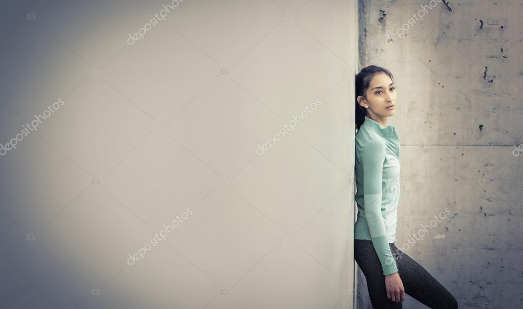Young Active Woman Leaning Against Wall Stock Photo