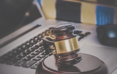 Gavel on computer with legal books