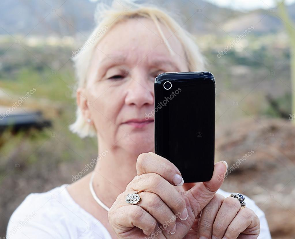Hip cool trendy grandma taking selfies with a smart phone