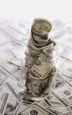 Glass jar with hundred dollar bill