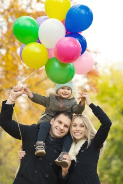 Happy family with little child and air-balloons, outing in autumn park stock vector