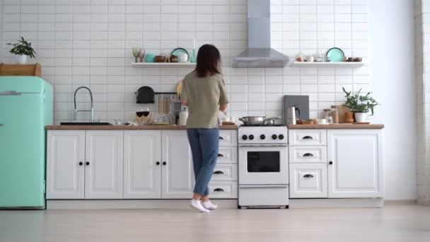 Carefree šťastná mladá žena tanec sám vaření jídlo v moderní kuchyni
