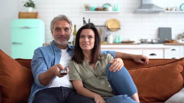 Pár koukání na televizi doma drží dálkové ovládání, užívají si spolu film