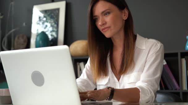 Sebevědomá podnikatelka pracující na laptopu ve své moderní kanceláři. Stylová krásná žena dělá důležitou práci