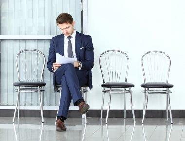 Thoughtful man in formalwear holding paper