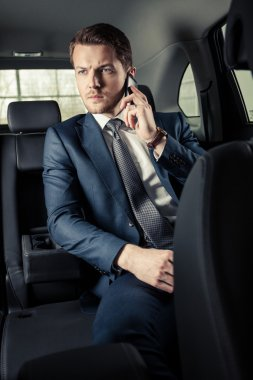 Businessman in the car with mobile phone