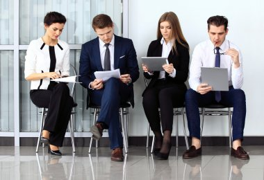 Business people waiting for job interview. Four candidates compe