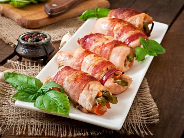 Delicious chicken rolls stuffed with green beans and carrots wrapped in strips of bacon stock vector