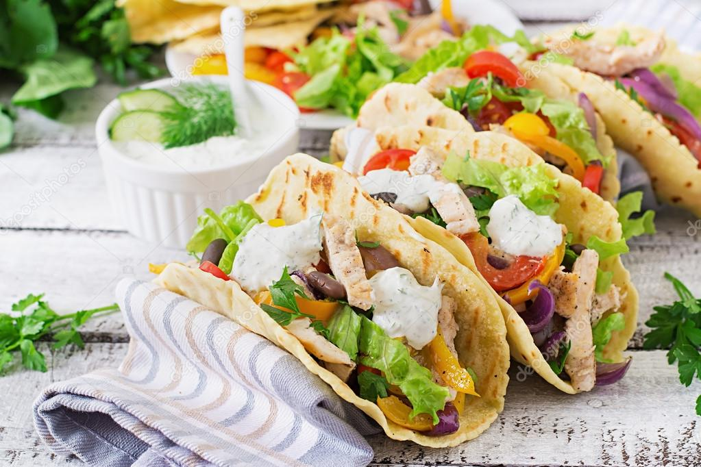 Mexican tacos with chicken, bell peppers, black beans and fresh vegetables and tartar sauce