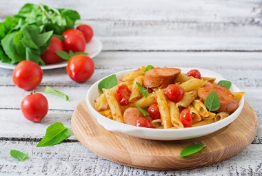 Penne pasta with tomato sauce with sausage, tomatoes, green basil decorated in a frying pan on a wooden background. stock vector