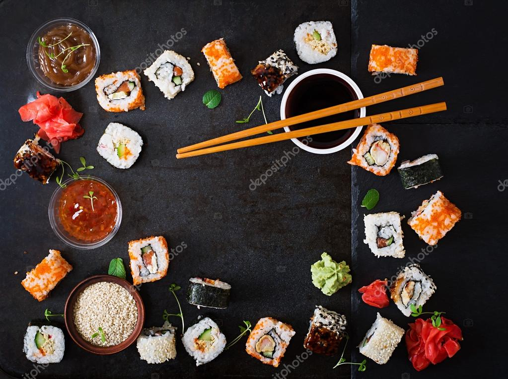 Traditional Japanese food - sushi, rolls and sauce on a dark background.
