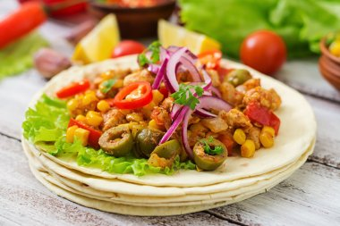 Mexican tacos with meat, corn and olives on wooden background