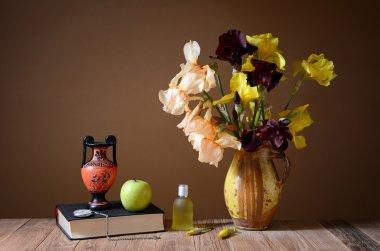 Yellow irises, amphorae, apple and book