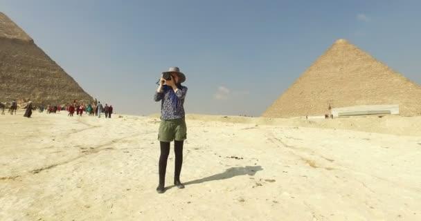 Woman taking photos at Giza pyramids