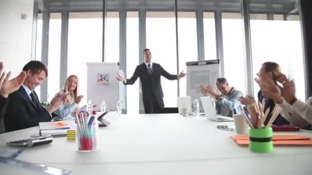 Colleagues applauding smiling businessman