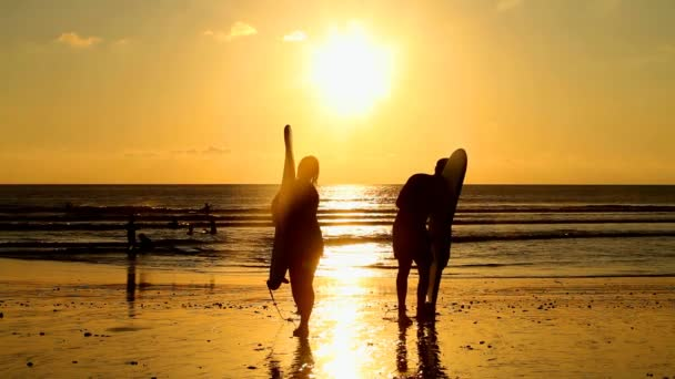 Surfer couple walking with long surf boards
