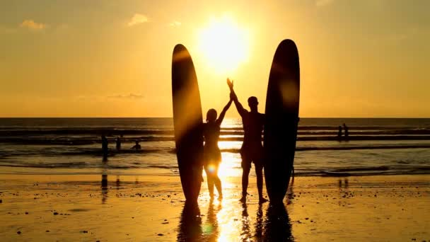Surfer couple holding long surf boards