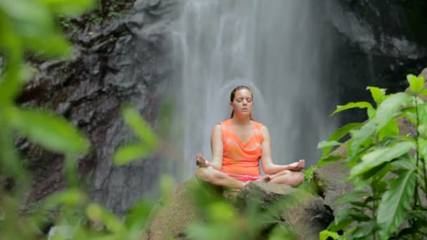 Woman sitting in meditation under waterfall