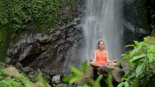 Frau sitzt in der Meditation unter Wasserfall