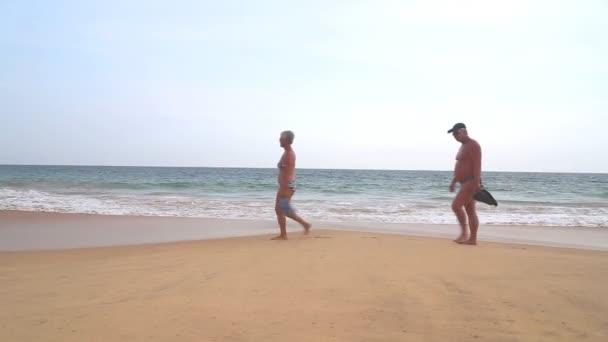 Elderly couple walking along beach