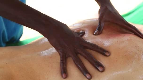 Sri Lankan man giving lower back oil massage to Caucasian man