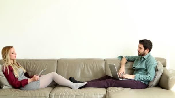 Pár beszél, és segítségével a számítógépek a kanapén