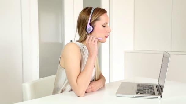 Žena se sluchátky na počítači, mluví se zákazníkem