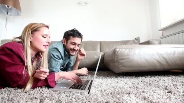 Paar auf dem Boden liegend und mit Laptop