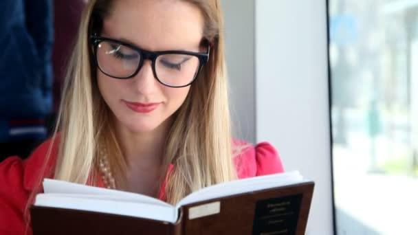 Nő ül, és az olvasás a villamoson