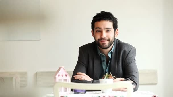 Pohledný mladý muž sedí v kavárně usmívá