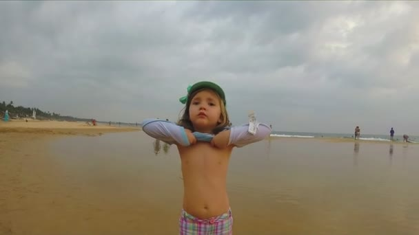 Little girl walking at the sandy beach