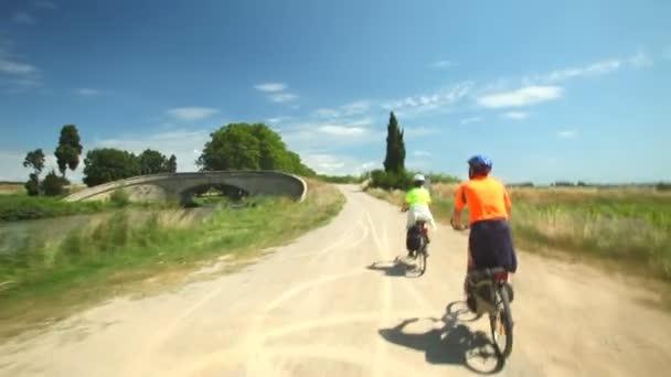 Pár na kole podél prašné cestě