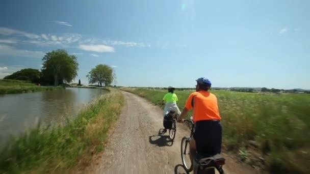 Důchodci pár cyklistické vedle řeky