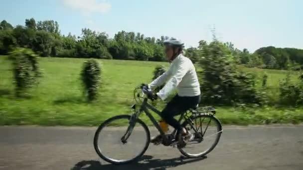 Žena na kole na silnici v krajině