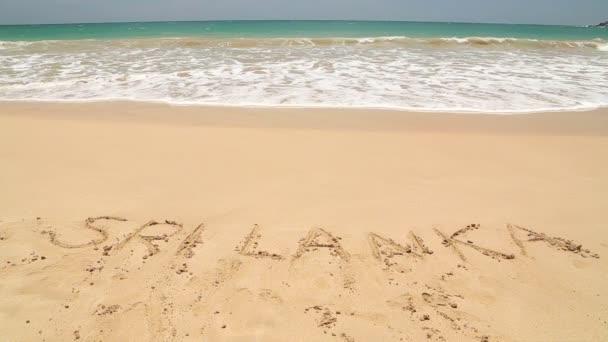 Ocean wave approaching words Sri Lanka written in sand on beach